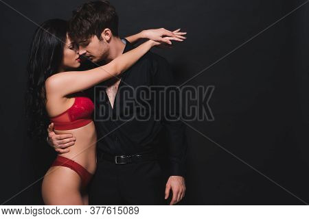 Seductive Woman In Red Bra And Panties Hugging Handsome Man Isolated On Black