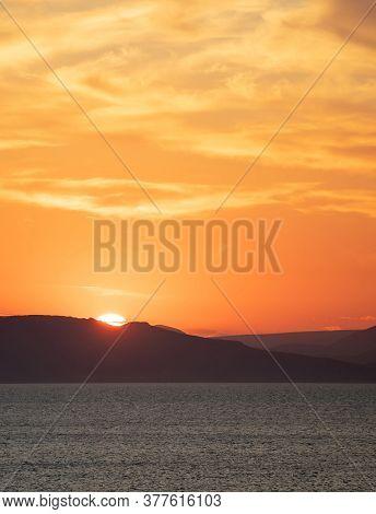 Sunrise, Sunset Clouds. Twilight, Dusk Cloudy Sky Over Sea Water, Mountain Silhouette