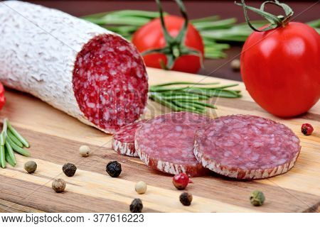 Close Up Of Salami With Cherry Tomatoes On A Cutting Board