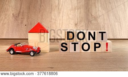 Dont Stop. Nadpist On Cubes On A Wooden Table. With Cubes Near Cars, And A House With Cubes.