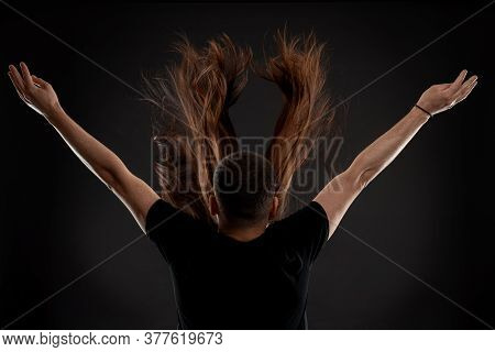 Young Hairstylist In Black T-shirt Stands Back To The Camera With Raised Hand Behinde Young Woman Wi