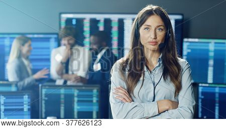 Portrait Of Female Stock Trader Or Brokers Working At Stock Exchange Office Using Headset And Lookin