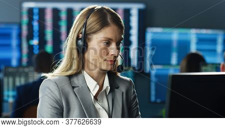 Portrait Of Female Stock Trader Operating At Her Workstation Using Headset And Computer On Backgroun