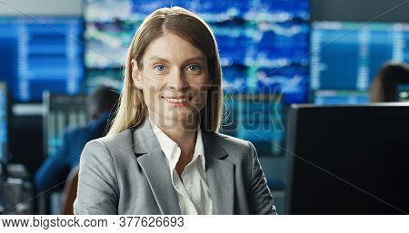 Portrait Of Female Stock Trader Operating At Her Workstation Using Computer On Background Of Multipl