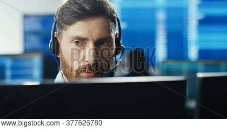 Portrait Of Male Trader Or Broker Working At Stock Exchange Office Using Headset And Computer On Bac