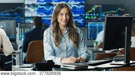 Portrait Of Female Stock Trader Operating At Her Workstation Using Computer And Looking At Camera On