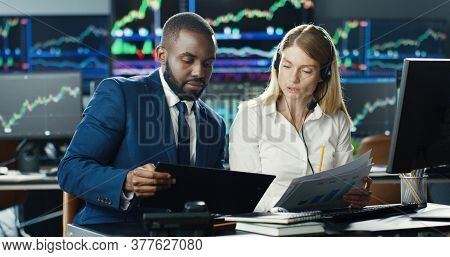 Portrait Of Traders And Brokers Working At Stock Exchange Office. Monitors Display Relevant Infograp
