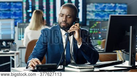 African American Male Stock Trader Working At Stock Exchange Office And Talking Phone On Background