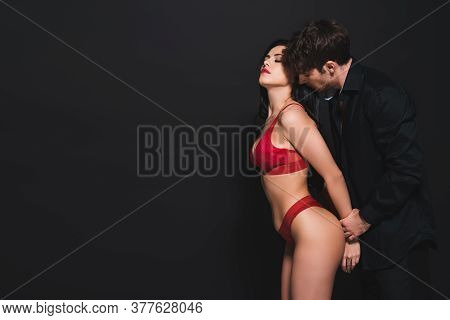 Dominant Man Touching Hands Of Submissive Woman In Red Lingerie On Black
