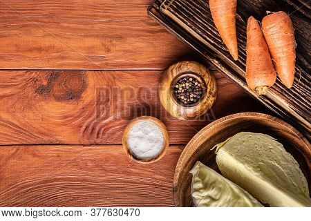Set Of Cabbage Fermenting Ingredients. Cabbage, Unpeeled Carrots, Pepper And Salt On Wooden Surfaces