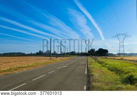 Countryside Landscape In Summer. High Voltage Electricity Pylons In The Middle Of The Fields.