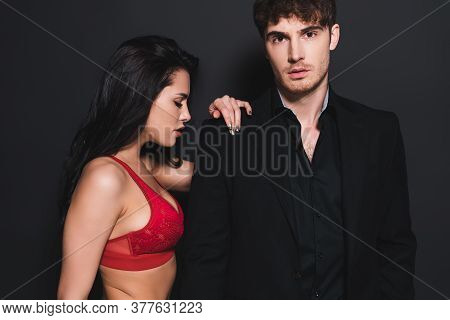 Sexy Woman In Red And Lace Bra Touching Handsome Man On Black