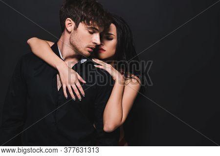 Seductive Woman Hugging Boyfriend Isolated On Black