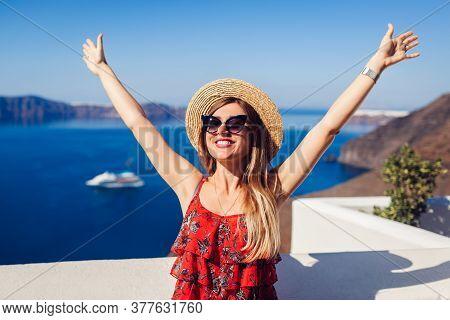 Woman Traveler Walking Raising Hands In Thera, Santorini Island, Greece. Tourism, Traveling, Summer