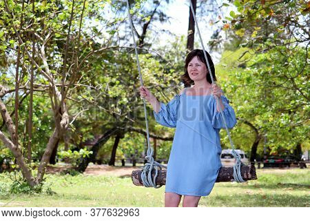 Happy Smiling Woman In Blue Dress Swinging On A Wooden Swing In The Tropical Park. Summer Holidays,