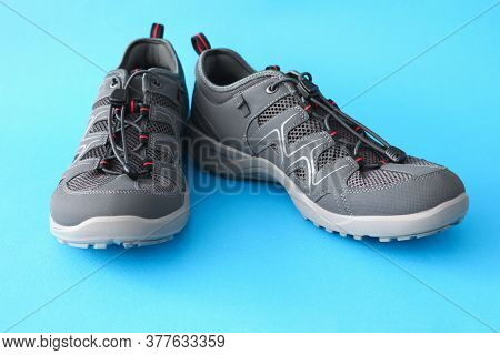 Close-up Of New Pair Of Grey Sneakers Standing On Blue Surface. Advertisement For Customer. Stylish