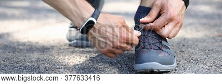 Close-up Of Sporty Male Person Hands Tying Up Shoelace. Stylish Grey Sneakers For Running. Man Ready