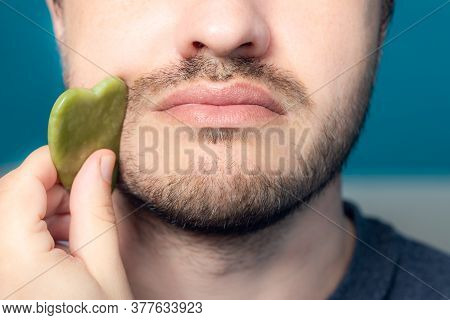 Bearded Man Is Using Jade Face Roller For Beauty Facial Massage Therapy