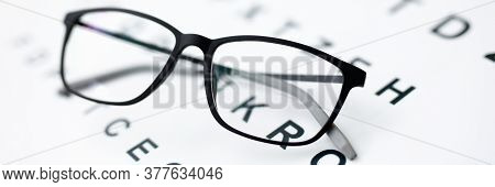 Close-up Of Black Glasses Laying On Paper With Letters. Thing For Better Vision. Check Sight. Simple