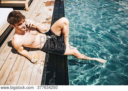 Young Hot Man Resting At Swimpool. Sexy Guy Lying On Edge Near Water And Talking On Phone. Resting A