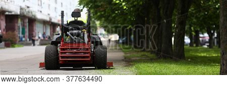 Close-up Of Professional Lawn Mower With Worker After Cutting Grass In City Park. Gardener Using Aut