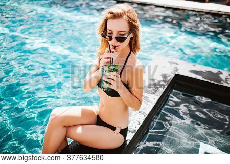 Young Hot Woman Resting At Swimpool. Up View Of Well-built Slim Girl In Sunglasses And Black Swimsui