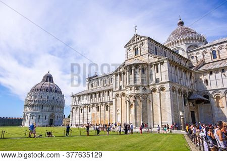Pisa, Italy - August 14, 2019: Large Group Of Tourists In Front Of The Baptistery And Pisa Cathedral