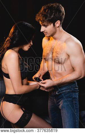 Dominant Man Tying Hands Of Seductive Woman With Ribbon Isolated On Black