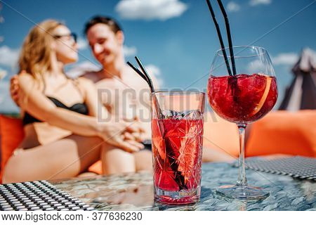 Young Hot Couple Resting At Swimpool. Low View And Blurred Picture Of Lovely Cheerful Man And Woman