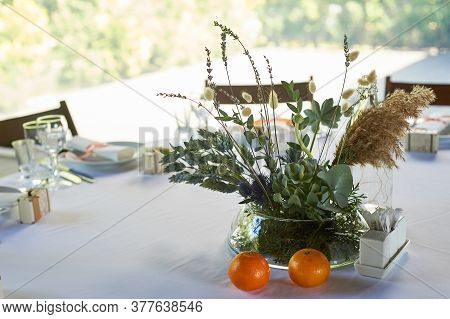 Composition Of Field Herbs And Cereals On The Table In The Restaurant In A Transparent Vase. White T