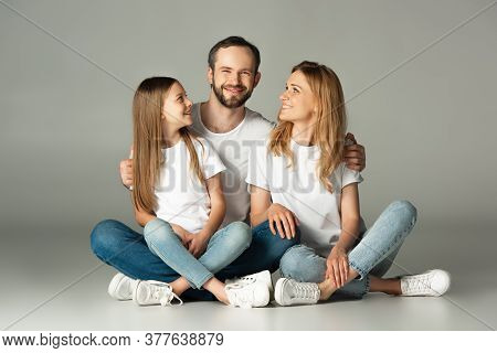 Happy Family Sitting On Floor With Crossed Legs And Embracing On Grey Background