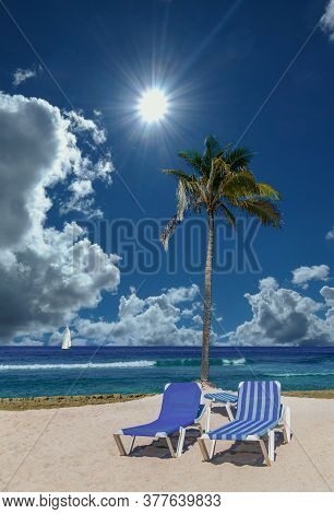 Two Chaise Lounges And Palm Tree On A Peaceful, Empty Beach
