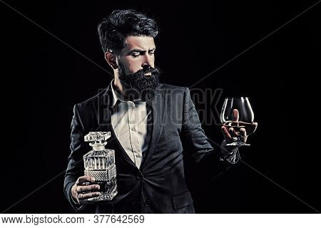 Bartender Leather Apron Holding Brandy Snifter. Hipster With Beard And Mustache In Suit Drinks Alcoh