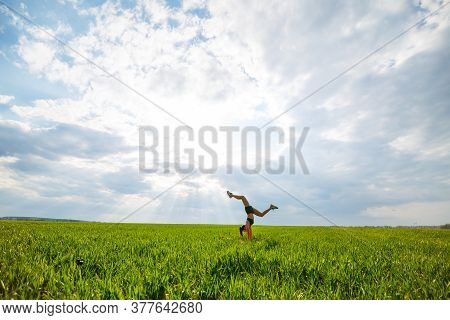 Beautiful Young Woman In A Black Top And Shorts Performs A Handstand. A Model Stands On Her Hands, D