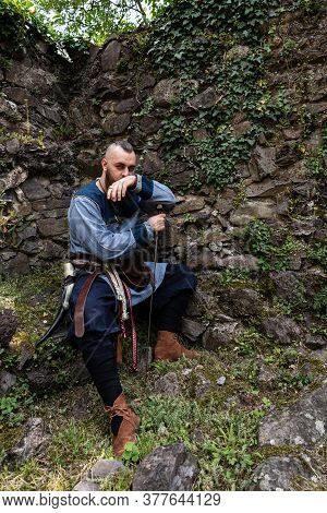 A Viking Sitting With His Sword In Front Of A Stone Wall, Full-length Portrait Of A Man In Historica