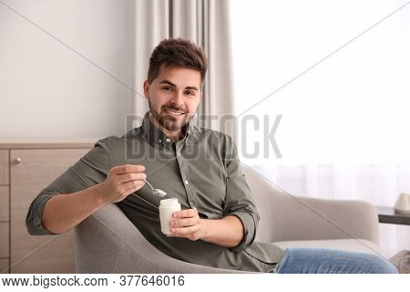 Happy Young Man With Tasty Yogurt In Living Room. Space For Text
