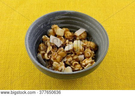 Tropical Caramel Popcorn Snack Mixture With Coconut And Dried Pineapple Chunks In Ceramic Bowl On Ye