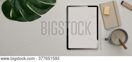 Office Desk With Mock Up Tablet, Stationery, Coffee Cup And Copy Space On White Table