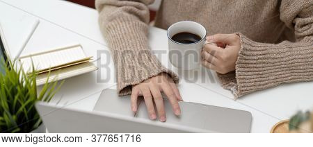 Female Using Laptop While Holding Coffee Up On White Table