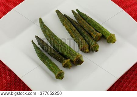 Soy Sauce Sesame Flavored Dried Okra Chips On White Snack Plate On Red Tablecloth