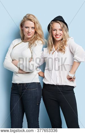 Portrait of two young female friends standing together against light blue background