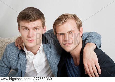 Close-up portrait of two young male friends with arms around