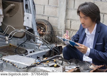 Asian Insurance Agent Or Insurance Agency In Suit Inspecting Car Crash From Accident And Write Repor