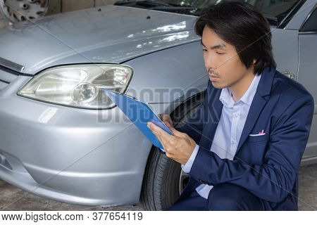 Asian Insurance Agent Or Insurance Agency In Suit Reading Report And Inspecting Car Crash From Accid