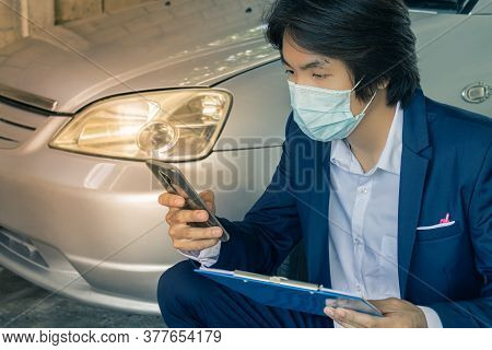 Sitting Asian Insurance Agent Or Insurance Agency In Suit Wear Mask And See Smartphone And Hold Repo