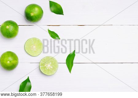 Flat Lay Natural Fresh Lime With Whole And Cut Lime Slices, Green Leaf On White Wooden Table Backgro