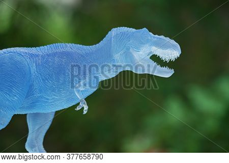 Frozen Dinosaurs On Nature Background. Tyrannosaurus Rex Dinosaurs Toy