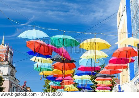 Different Colorful Umbrellas Hanging Over The Street Against Blue Sky