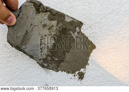 Worker Spreading Mortar Over Styrofoam With Spatula