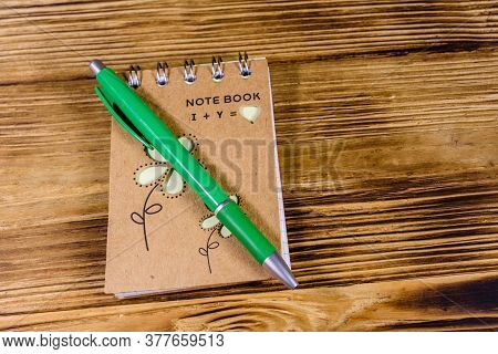 Closed Small Notepad And Ball Pen On Rustic Wooden Table. Top View